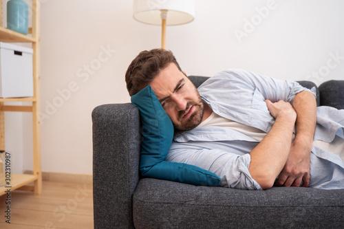 Photo Man portrait suffering stomach ache at home