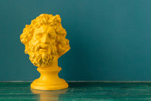 Yellow Male Head With Beard And Long Hair Of The Ancient Sculpture On A Floor Against Blue Wall Background
