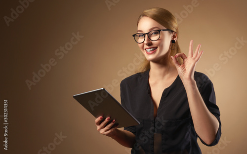 Valokuvatapetti Happy professional girl wearing glasses and holding tablet isolated on brown bac