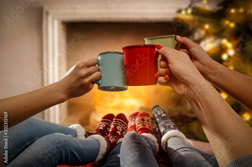 Foto auf Leinwand Kaffee Woman legs with christms socks. Free space for your decoration. Xmas tree and fireplace.