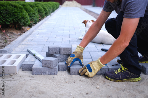 Fototapeta The master in yellow gloves lays paving stones in layers