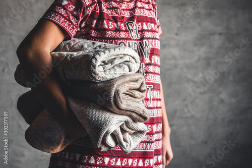 A girl in a Christmas dress holds a stack of sweaters Tablou Canvas