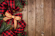 canvas print picture Christmas side border with red and black checked buffalo plaid ribbon, burlap and tree branches. Overhead view on a rustic wood background.