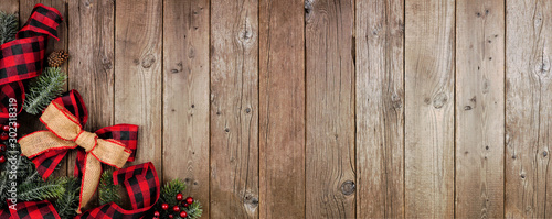 Christmas corner border banner with red and black checked buffalo plaid ribbon, burlap and tree branches. Top view on a rustic wood background. - 302318319