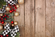 Christmas Side Border With White And Black Checked Buffalo Plaid Ribbon, Decorations And Tree Branches. Overhead View On A Rustic Wood Background.