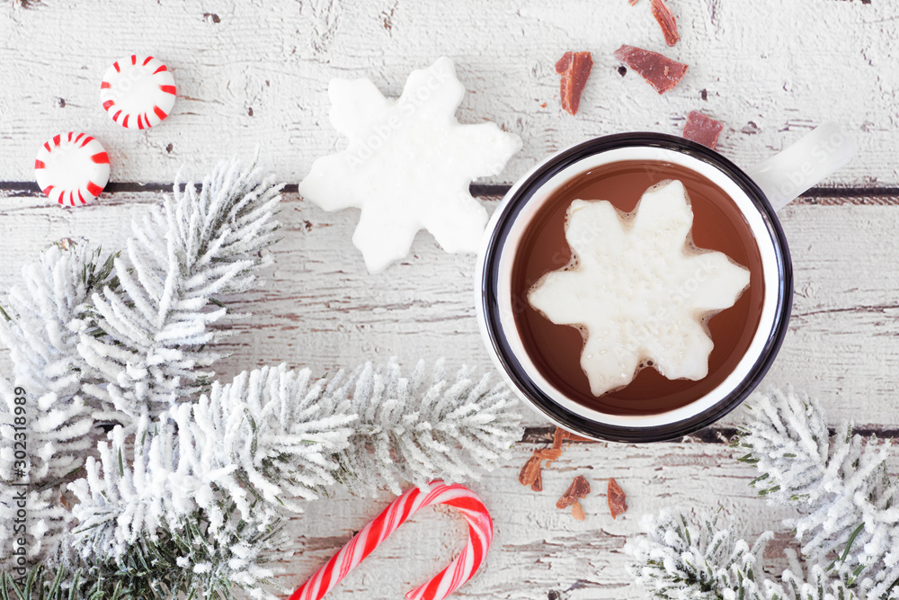 Fototapety, obrazy: Hot chocolate with snowflake marshmallow. Top view table scene with snowy branches and candy against a white wood background.