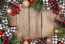 Christmas Frame With White And Black Checked Buffalo Plaid Ribbon, Baubles And Tree Branches. Top View On A Rustic Wood Background.