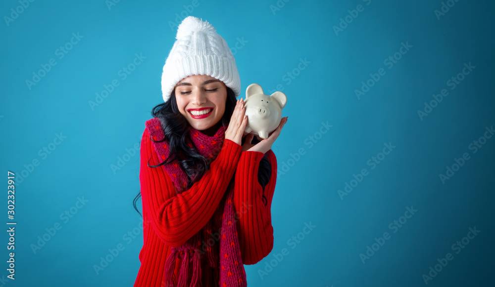 Fotografie, Tablou  Young woman in winter clothes with a piggy bank on a dark blue background