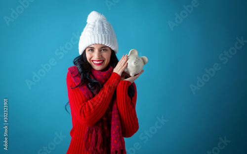 Young woman in winter clothes with a piggy bank on a dark blue background Fototapet