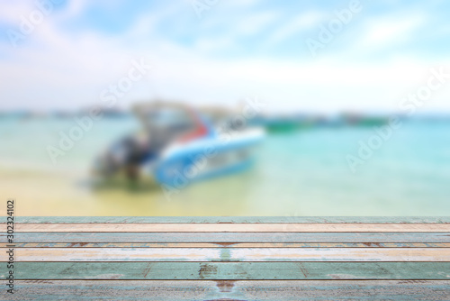 Fotografía  Wood table top with blurred boat at the beach