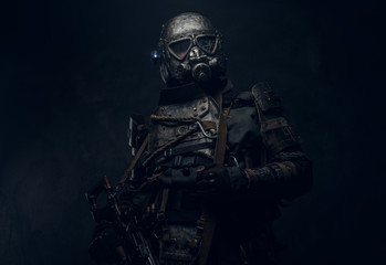 Cool cosplay costume of post - apocalypse knight, man is posing at dark photo studio.