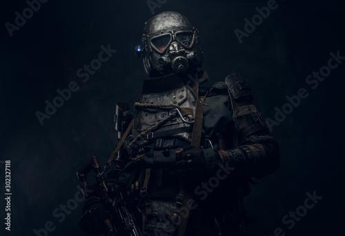 Cool cosplay costume of post - apocalypse knight, man is posing at dark photo studio Canvas Print