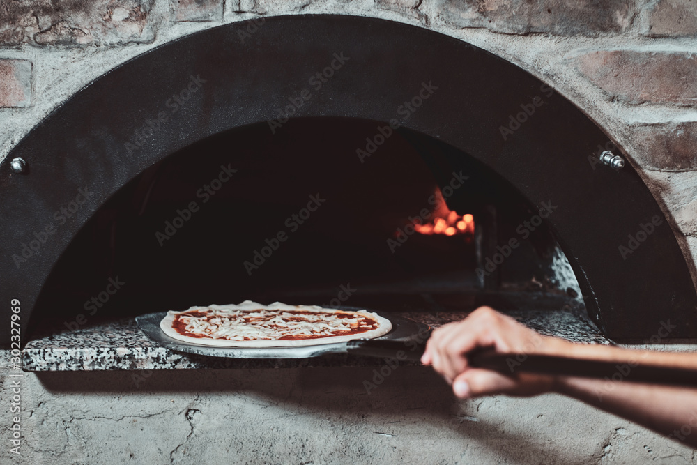 Fototapety, obrazy: Italian chef is putting prepared margarita pizza to the oven with flame in it.