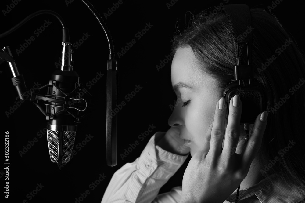 Fototapety, obrazy: Recording female vocals. Young girl with a microphone and headphones in a recording studio. Vocal recording, blogger, reading text, voice acting. Vertical frame, with dramatic light in black and white