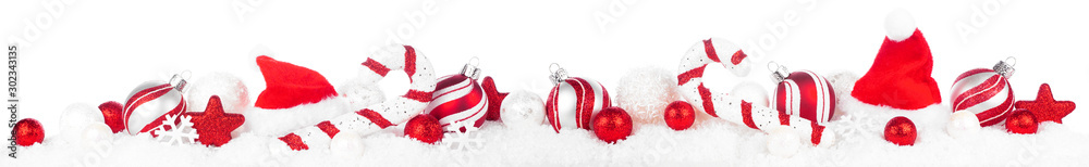 Fototapeta Christmas border of red and white decorations in snow. Side view isolated on a white background.