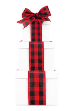 Stacked White Christmas Gift Boxes With Red And Black Buffalo Plaid Bow And Ribbon. Side View Isolated On A White Background.