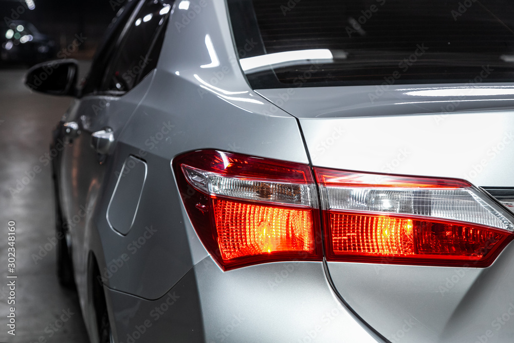 Fototapeta Macro view of modern silver car xenon lamp taillight, bumper, rear trunk lid. Exterior of a modern car