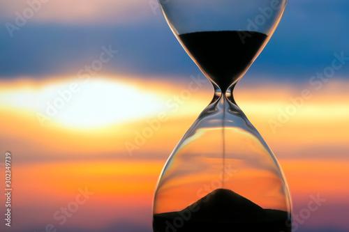 Obraz na plátně Hourglass on the background of a sunset