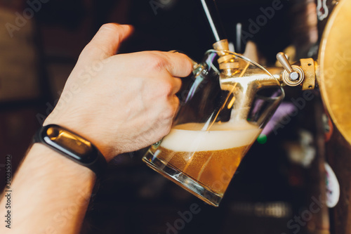 Photo close-up of barman hand at beer tap pouring a draught lager beer.