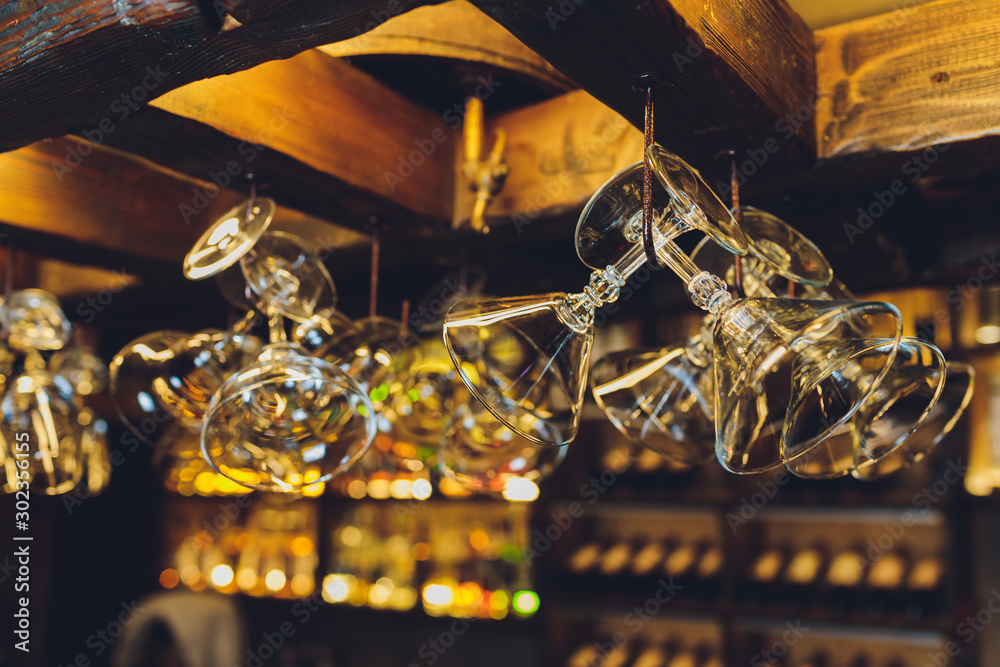Fototapety, obrazy: Group of empty wine glasses hanging from metal beams in a bar.