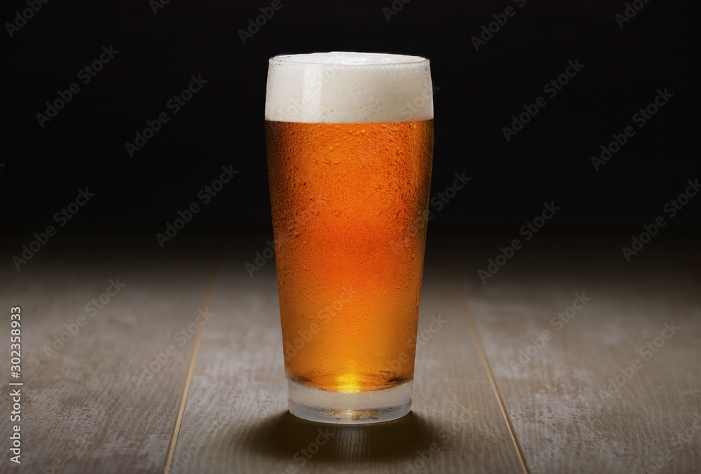 Fototapety, obrazy: Double India pale ale beer served in a chilled pint glass on wooden counter at a craft beer pub, black background