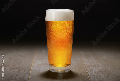 Платно A fresh pint of India Pale ale IPA craft beer served in a cold pint glass at a b