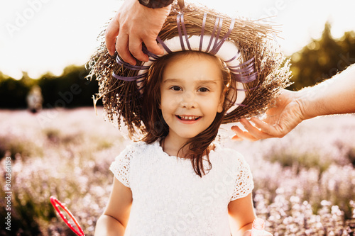 Fotografia, Obraz  Portrait of a lovely little girl looking at camera smiling outdoor while her father is putting a crown from flowers in a file d of flowers