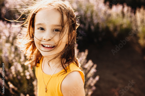 Fototapeta  Portrait of a lovely little girl looking at camera laughing while being in a field of flowers against sunset dressed in yellow