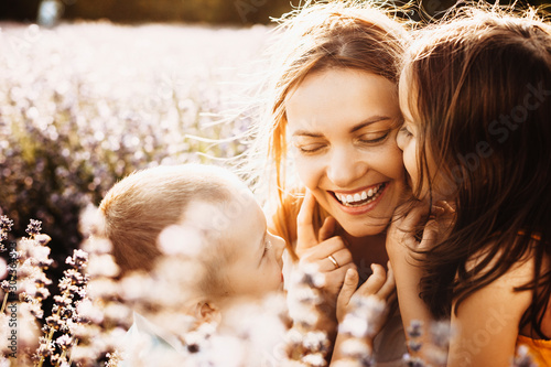 Fototapeta Beautiful young mother laughing while her kids are embracing and kissing her outside in a field of flowers against sunset. obraz