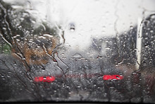 Drops Of Rain Drizzle On The Glass Windshield In The Evening. Street In The Heavy Rain. Bokeh Tail Light And Traffic Lights In City. Please Drive  Car Carefully, Slippery Road. Soft Focus.