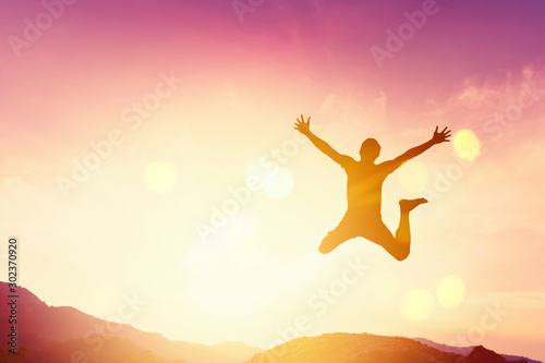 Photo Happy man jumping at top of mountain with sunset sky abstract background