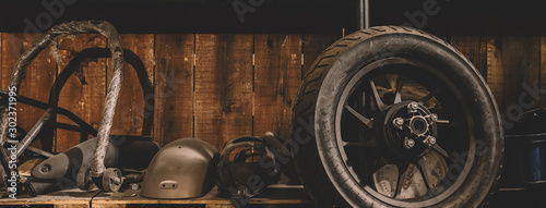 Motorcycle wheel on the floor with workshop tools, vintage garage, with blank copy space