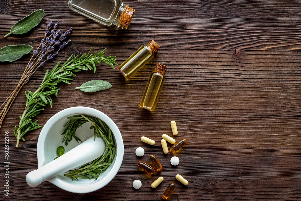 Fototapeta Medicine made from wildflowers and herbs with essential oils -pattern with mortar and pestle on dark wooden background top view copy space