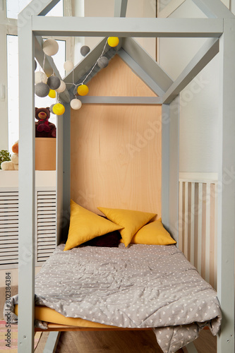 фотография Cozy baby crib and pillows with a canopy in soft colors
