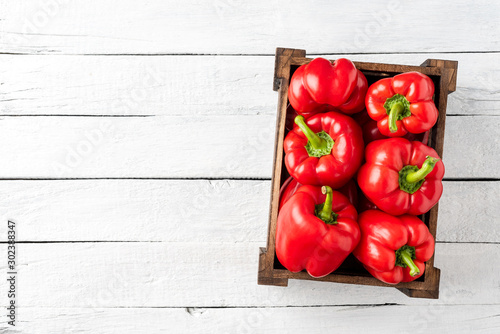 Fotografija Overhead shot of red bell pepper in box on white wooden table with copyspace