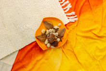 Orange Bowl With Aromatic Decorations On White Carpet And Fabric, Flatlay