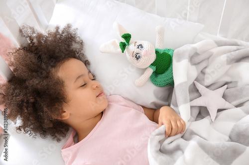 Obraz Little African-American girl sleeping in bed - fototapety do salonu