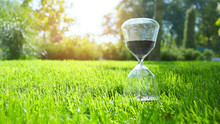 Hourglass On Green Grass Outdo...