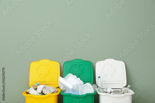 Fotografia, Obraz  Containers with different types of garbage near color wall