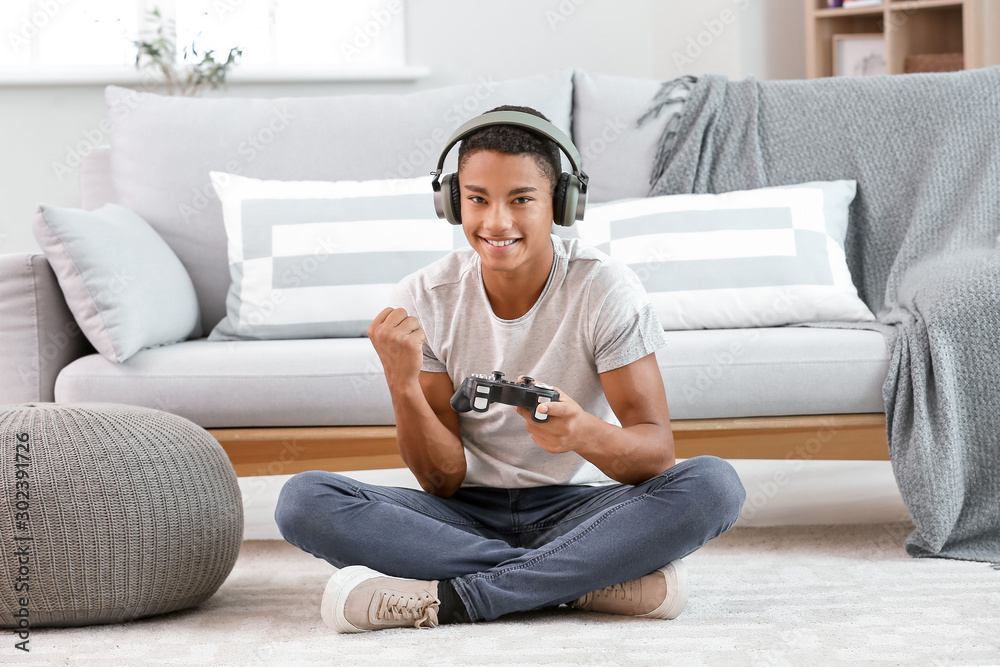 Fototapeta Happy African-American teenager boy playing video games at home