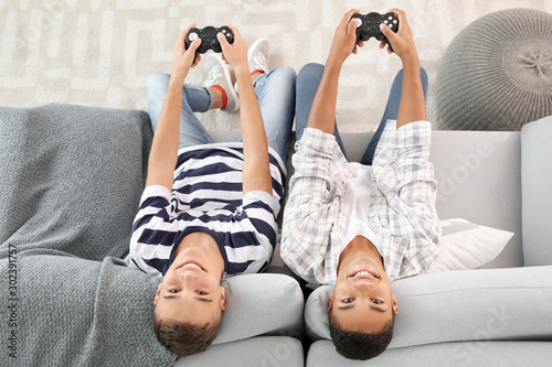 Obraz Teenager boys playing video games at home, top view - fototapety do salonu