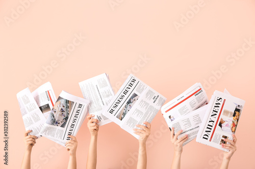 Female hands with newspapers on color background Poster Mural XXL