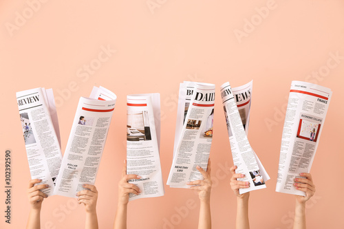 Foto Female hands with newspapers on color background
