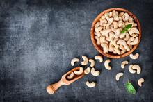 Cashew Nuts In Wooden Bowl On Dark Stone Table With Mint Leaf On Top.
