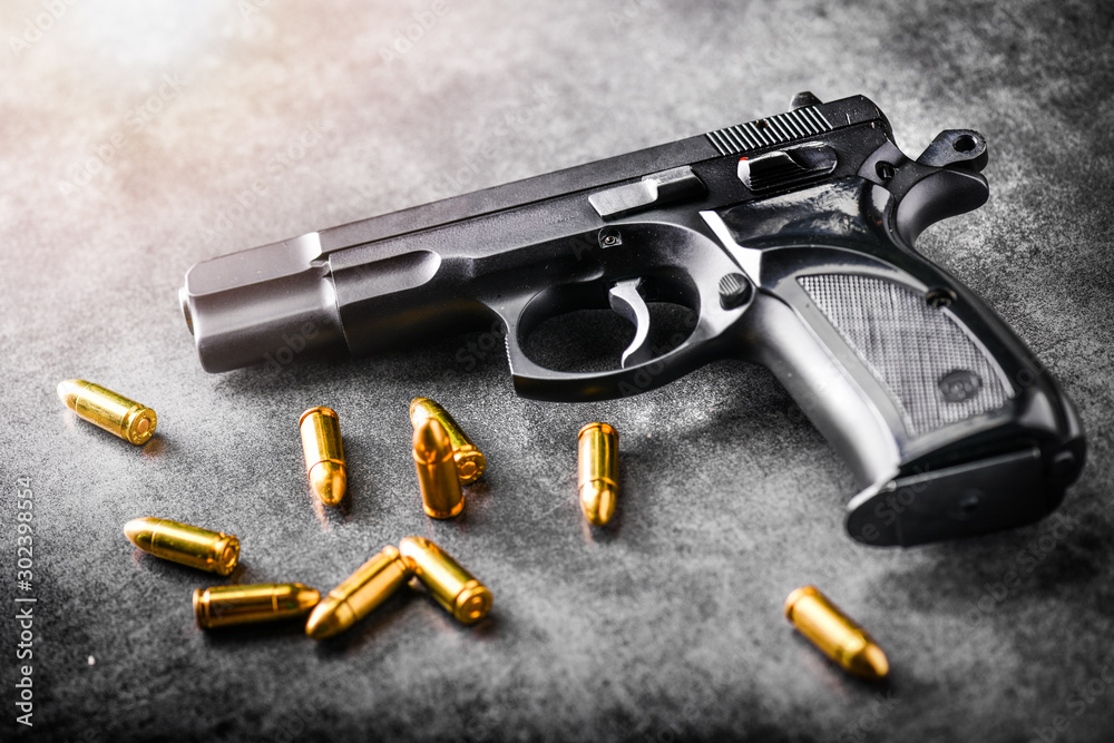 Fototapeta Hand gun with ammunition on dark stone background. 9 mm pistol gun military weapon and pile of bullets at the metal table.