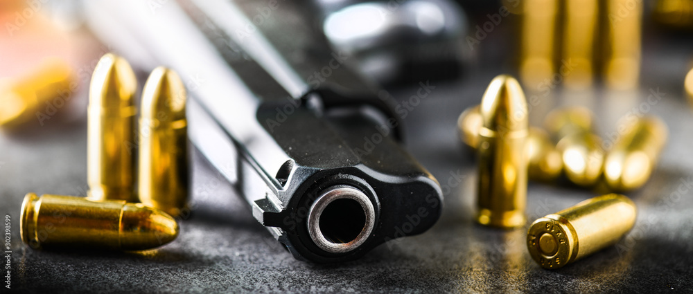Fototapeta Hand gun detail with ammunition on stone table banner or panorama photo. 9 mm pistol gun weapon and bullets at dark background.