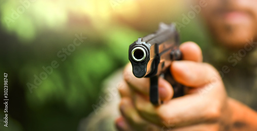 Foto  Army man hold a 9mm gun prepare to fire on target