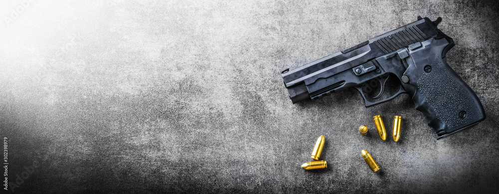 Fototapeta Hand gun banner or panorama pfoto on dark stone table top view. Ammunition or bullets at black background. Copy space for text concept.
