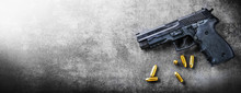 Hand Gun Banner Or Panorama Pfoto On Dark Stone Table Top View. Ammunition Or Bullets At Black Background. Copy Space For Text Concept.