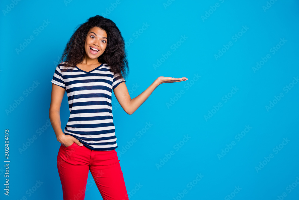 Fototapety, obrazy: Photo of cheerful positive nice pretty cute attractive girlfriend holding hand in pocket holding empty space smiling toothily in striped t-shirt isolated over vivid blue color background